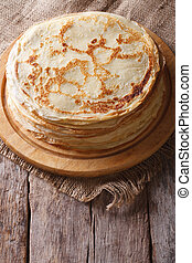 pile of crepes on a board on the table. Vertical top view - ...