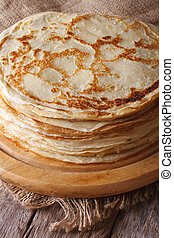 pile of crepes on a kitchen board on the table. Vertical - ...