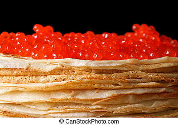 Pile of crepes with red caviar macro isolated on black