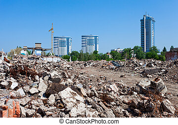 Pile of debris of ruined building on new buildings...
