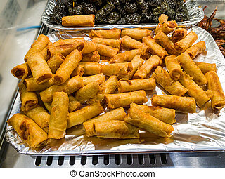Pile of deep-fried spring rolls on food tray at hypermarket