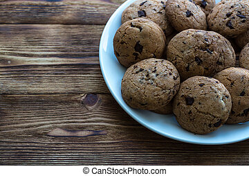 Pile of Delicious Chocolate Chip Cookies on a plate on wooden table