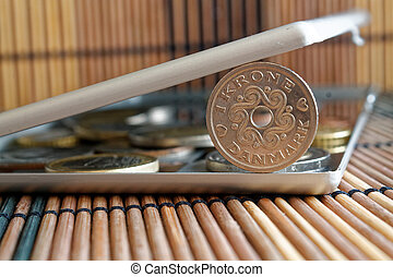 Pile of Denmark coins with a denomination of 1 krone (crown) in mirror reflect wallet lies on wooden bamboo table background