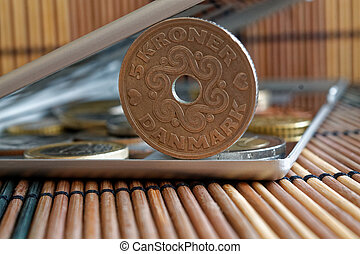 Pile of Denmark coins with a denomination of 5 krone (crown) in mirror reflect wallet lies on wooden bamboo table background