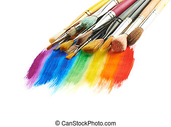 Pile of the multiple different brushes over the rainbow gradient paint strokes, composition isolated over the white surface