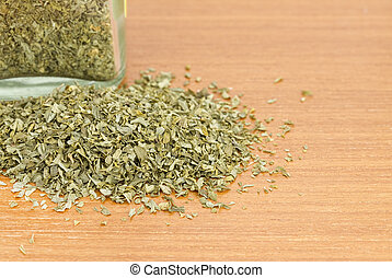 Pile of dried parsley with jar on wooden worktop