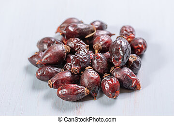 pile of dry rose hips on a wooden table