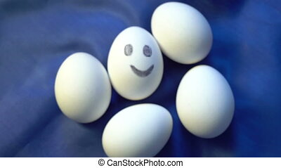 Pile of eggs, one smiling, different, standing out from faceless the crowd, individuality, positive energy