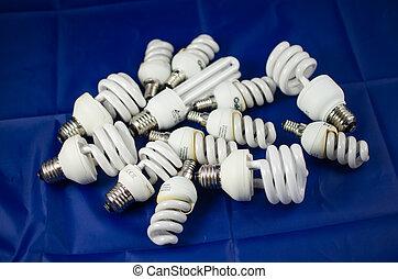 energy saving lamps - pile of energy saving lamps on blue...