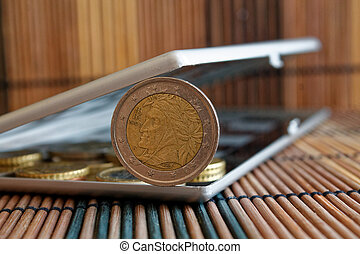 Pile of Euro coins in mirror reflect wallet lies on wooden bamboo table background Denomination is two euro - back side