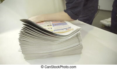 pile of finished newspapers is wrapped in printing plant.