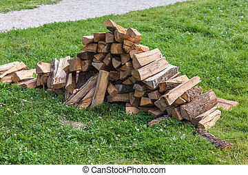 Pile of firewood on green grass background