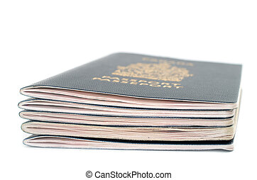 Pile of five passports viewed from the side on white bacground