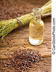 Pile of flax seeds in front of bowl with flaxoil
