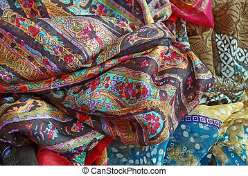 Pile of folded colour fabrics and shawls (scarfs) at the market