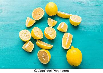 Pile of fresh lemons on turquoise wooden table.