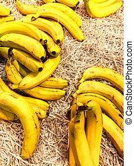 Pile of fresh organic yellow bananas on a market close up