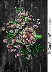 Pile of fresh pink clover flower heads on wooden background, top view. Natural herbal remedy