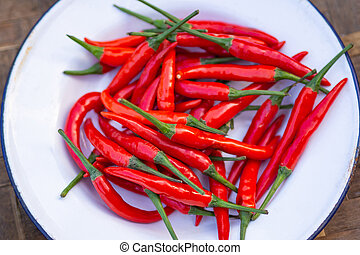 Pile of fresh red chilies pepper on white plate