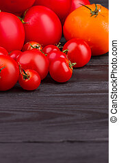 Pile of fresh tomatoes on dark wooden background.