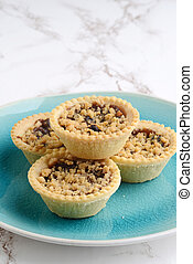 fruit tarts with crumble topping on blue plate