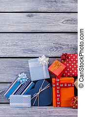 Pile of gift boxes on wooden background.