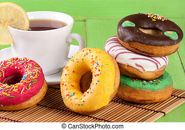 pile of glazed donuts with a cup of tea on a green wooden background