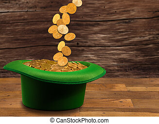 Pile of gold coins inside green hat St Patricks Day -...