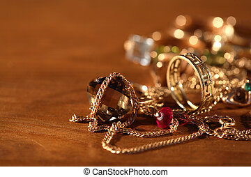 Closeup of pile of gold jewelry on wooden surface with lighting effect