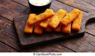 Pile of golden fried fish fingers with white garlic sauce...