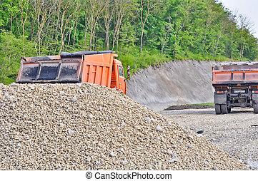 pile of gravel and dump trucks