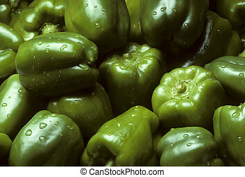 Pile of green Bell peppers with water droplets