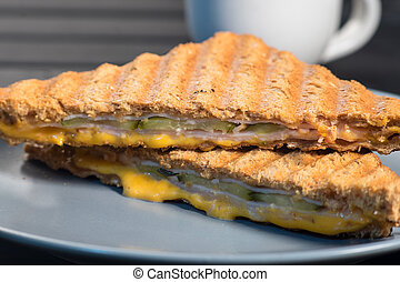 Pile of grilled sandwiches with cheese and ham.