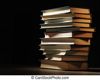 Pile of hardcover books in a shadowy room - Pile of...