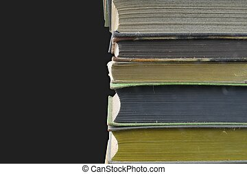 Pile of hardcover vintage books isolated with copy space. Black background. Close-up