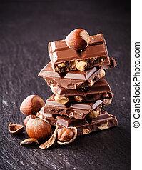Pile of hazelnut chocolate on black background - Pile of...
