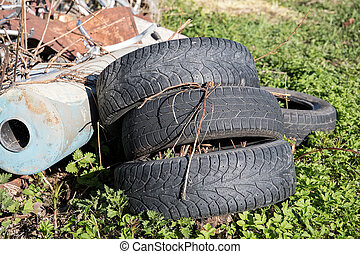 Pile of many old, used tires in the green grass