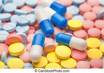 pile of medical pills in different colors and white-blue ...
