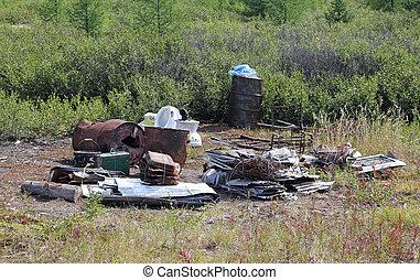 pile of metal garbage in a natural field