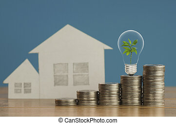 pile of money coins with small green tree, light bulb and paper home, on wood and soft blue background, concept in fiance, loan and buying
