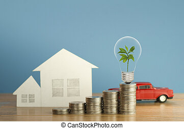 pile of money coins with small green tree, light bulb, toy car and paper home, on wood and soft blue background, concept in fiance, loan and buying