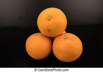 Pile of Naval Oranges on black background