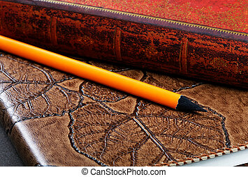 Pile of notebooks in leather covers and a pencil close up