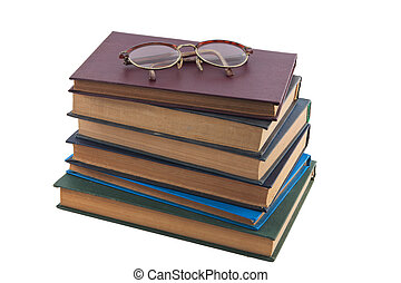 pile of old books and vintage glasses
