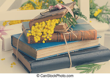 vintage old books with french mimosa flowers, retro toned
