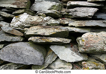 pile of old, mossy gray rocks from a foundation wall