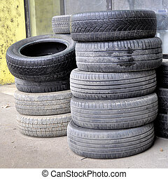 pile of old used car tires arranged in high piles