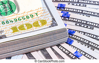 Pile of one hundred american dollar banknotes over money background, close up