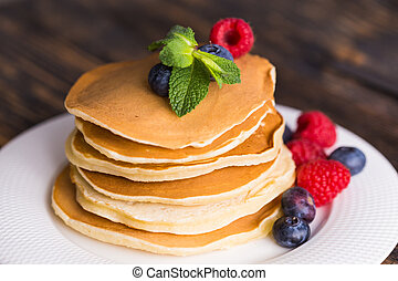Pile of pancakes with blueberries and raspberries for breakfast on wooden table.