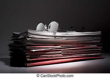 Pile of paperwork - Reading glasses on a stack of papers and...